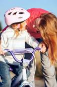 Redhead girl in helmet learning riding bike. — Stock Photo