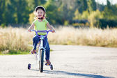 Small funny kid riding bike with training wheels. — Stock Photo