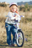 Small funny kid riding bike with training wheels. — Стоковое фото
