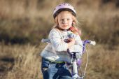 Small funny kid riding bike with training wheels. — Stockfoto