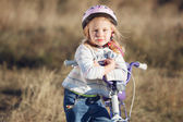 Small funny kid riding bike with training wheels. — Stock fotografie