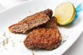 Fried veal medallion cut with lemon. — Stock Photo