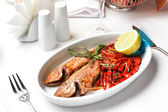 Fried fish with red peppers and lemon. — Stock Photo