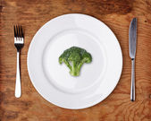 Knife, Fork and plate with broccoli on wooden table. — Photo