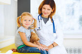 Portrait of pediatrician and little girl patient. — Photo