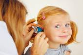 Pediatrician doctor examining little girl ears. — Stock Photo