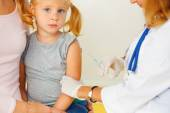 Doctor vaccinating small redhead girl. — Stock Photo