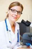 Portrait of beautiful young doctor in a laboratory looking at ca — Stockfoto