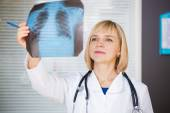 Portrait of confident doctor looking at xray. — Stock Photo