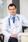 Portrait of confident doctor with stethoscope looking at the cam — Stock Photo