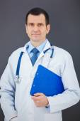 Portrait of confident doctor on gray background looking at the c — Stock Photo