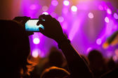 People at concert shooting video or photo. — Stock Photo