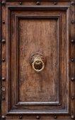 Dark wooden door panel with door knocker. — Stock Photo