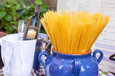 Composition with Spaghetti in vase and bottle of red wine. — Stock Photo