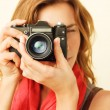 Young redhead woman looking through viewfinder with an old 35mm — Stock Photo #68104971