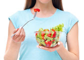 Portrait of a fit healthy woman eating a fresh salad isolated on — Stock Photo