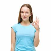 Portrait of a woman showing ok sign and smiling isolated on whit — Stock Photo