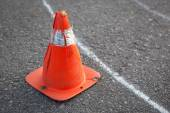 Old orange striped cone on road. — Stock Photo