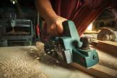Carpenter working with electric planer. — Stock Photo