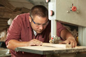 Professional carpenter working with sawing machine. — Stock Photo