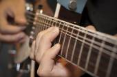 Close up shot of a man with his fingers on the frets of a guitar — Stock Photo