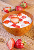 Fresh organic yogurt with strawberry on wood — Stock Photo