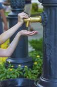 Closeup photo of girl hands push a city fountain — Stock Photo