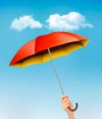 Hand holding a red and yellow umbrella against a blue sky with c — Stock Vector