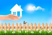 The house in hand on green natural background. Vector.  — Stock Vector