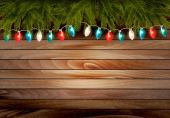 Christmas wooden background with branches and a garland. Vector  — Stockvector