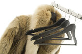 Coat hangers and a fur coat on a clothing rail — Zdjęcie stockowe