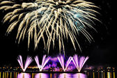 Firework over city at night with reflection in water — Stock Photo