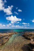 Rocky coast of Cyprus. Blue sky and white clouds. — Stock Photo
