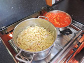 Cooking pasta with sausage and meat gravy on stove — Stock Photo