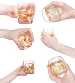Set of hand holds whiskey on ice in glass isolated — Stock Photo