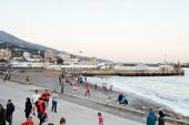 Tourists on pebble beach of Yalta city in evening — Stock Photo