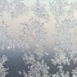 Frost patterns on window glass at winter sunrise — Stock Photo #58902761