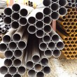 Heap of metal pipes in outdoor warehouse — Stock Photo #60169507