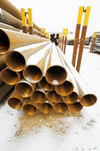 Rusty steel pipes in stacks on outdoor warehouse — Stock Photo