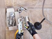 Plumber repairs sink trap in bathroom — Stock Photo