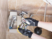 Sanitary technician replaces plumbing trap of sink — Stock Photo