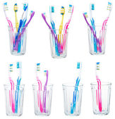 Collection of tooth brushes in clear glases — Stock Photo