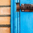 Closed metal latch on blue painted woooden door — Stock Photo #65254381