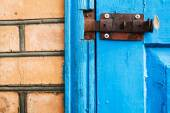 Closed metal latch on blue painted woooden door — Stock Photo