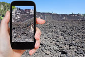 Tourist taking photo of lava flow on slope of Etna — Stock Photo