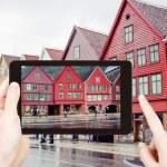 Tourist taking photo of Bryggen quay in Bergen — Stock Photo #66840973