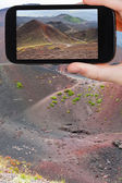 Tourist taking photo of path on slope of craters — Stock Photo