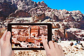Tourist taking photo of tombs and houses in Petra — Stock Photo