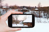 Tourist photographs of snowy wooden houses — Stock Photo