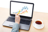 Laptop with graph on screen on office table — Stock Photo